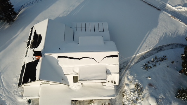 Gården i vinterskrud. När solen tittar fram lossnar snön snabbt och glider av panelerna.